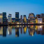 Modernia arkkitehtuuria merenpintaan heijastuen iltavalaistuksessa.