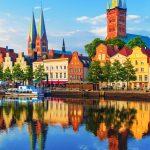 Värikkäitä rakennuksia joen rannalla.