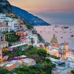 Amalfin rannikolla vuoren rinnettä ylösnouseva kaupunki on illan hämyssä. Merenlahdella jahdit ja purjeveneet ankkurissa.