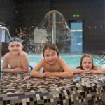 Kolme lasta nojaa altaan reunaan Medical Span allasosastolla