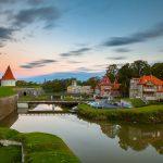 Piispanlinnan torni, joki, silta ja saari vanhoine rakennuksineen auringon noustessa.