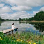 Nainen istumassa laiturilla Latgave järven rannalla