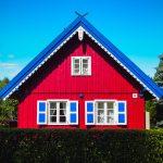 Punainen puutalo sinivalkoisilla somistuksilla Klaipedassa