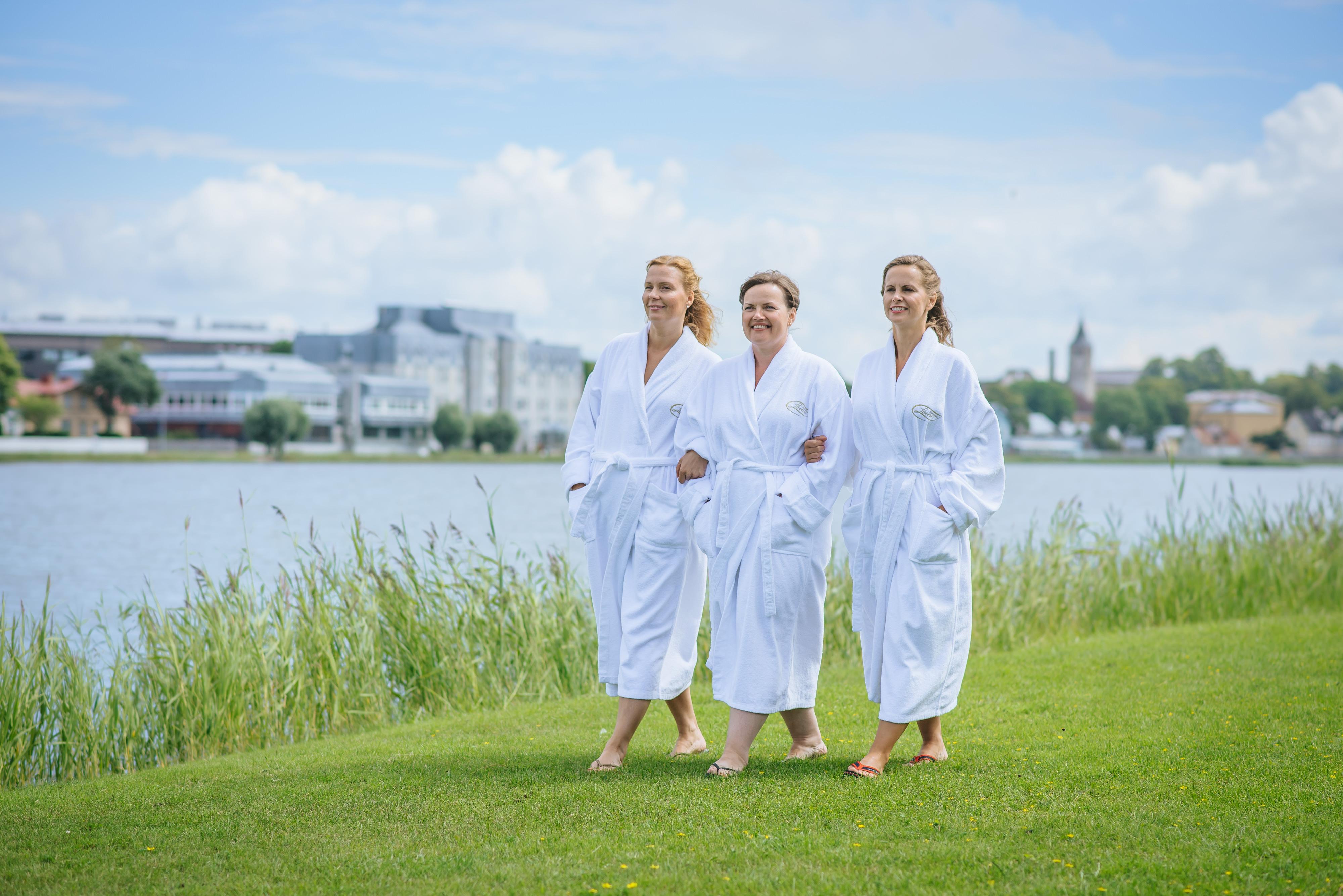 Kolme naista Laine-kylpylän aamutakeissa merenrannalla kesäisessä säässä