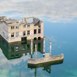 Rummun hylätty rakennus keskellä kirkasvetistä järveä