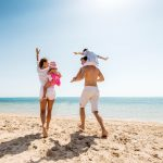 Iloiset vanhemmat nauttivat rannasta lastensa kanssa. Mies kantaa pientä poikaa harteilaan,