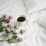 L'Embitu hotellin romanttinen huone, valkoisella lakanalla ruusuja ja kupillinen kahvia