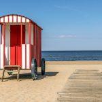 Punavalkoinen rantakärry hiekkarannalla puisen kävelylaiturin vieressä, taustalla meri.