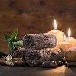 Kaunis asetelma, jossa kynttilöitä, kolme rullattua ruskeaa pyyhettä, hierontakiviä ja suolaa. Kaikki valmiina hemmotteluhoitoon.