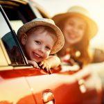 Hattupäiset pieni poika ja äiti hymyilevät iloisina ja kurkistavat auton ikkunoista.