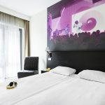 Comfort Hotel LT:n standard huone, jonka sängyn päädyn seinää koristaa värikäs maalaus discosta