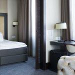 Comfort Hotel LT:n sviitin makuuhuone liukuovien takana