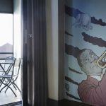 Comfort Hotel LT:n sviitin seinää koristaa suuri maalaus jossa trumpetista ja lentävä norsu. Parvekkeen ovi on auki.
