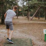 Poika heittää frisbeegolf kiekkoa radalla