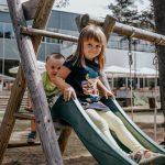 Tyttö ja poika laskevat liukumäkeä Laulasmaa Span lasten leikkikentällä