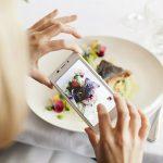 Nainen ottaa kännykällä kuvaa ravintola Wiccan herkullisesta ruoka-annoksesta