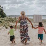 Isoäiti ja lapsenlapset juoksevat rantahietikolla käsi kädessä