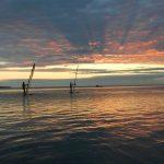 Kolme lainelautailijaa vesillä auringonlaskussa