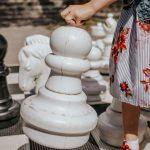 Pieni tyttö siirtää jättikokoista valkoista shakkinappulaa ulkopelilaudalla