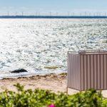 Laulasmaan rannalla seisoo puna-valkoraidallinen uimavaatteidenvaihtokoppi, niemenkärjessä siintää rivi tuulimyllyjä