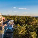 Ilmakuva Laulasmaa Span päärakennuksen parvekkeista, ympärillä mäntymetsää ja metsän takana meri