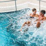 Pariskunta nauttii uima-altaan vesihierontapisteestä