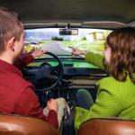 Kaksi henkilöä ajamassa Trabantilla