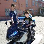 Poika istuu poliisimoottoripyörän selässä poliisimuseon pihassa
