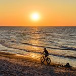 Pyöräilijä polkee rannalla auringon laskiessa.