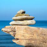 Neljä litteää kiveä pinottuna ajopuun päälle rannalla.