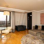 Sviitin tilavassa olohuoneessa on sohva, pöytäryhmä sekä parveke, josta näköala kaupunkiin