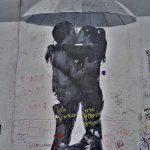 Berliininmuurissa maalattuna pariskunta suutelemassa