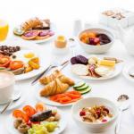 Valkoisella liinalla aamiaisvalikoimaa, kuten kahvia, mysliä, pekonia ja croissanteja.