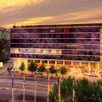 Nordic Hotel Forumin violettilasinen julkisivu auringonlaskussa