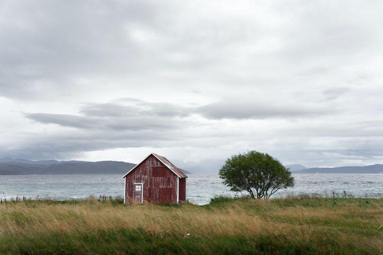 Vanha punainen lato meren äärellä tuulisena ja pilvisenä päivänä