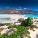 Turkoosin sinistä vettä, rannalla olijoita vuoristoa ja valkoista hiekkaa