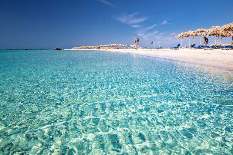Vaalealla rantahiekalla aurinkotuoleja turkoosin sinisen veden äärellä