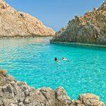 Mies ja nainen uimassa kirkkaan turkoosissa vedessä upeiden kallioiden keskellä