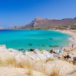 Turkoosia vettä, valkoista hiekkarantaa ja rannalla olijoita