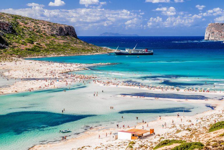 Sinisen veden äärellä rannalla olijoita nauttimassa lämmöstä ja auringosta