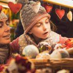 Tyttö ja äiti joulumarkkinoiden myyntikojulla