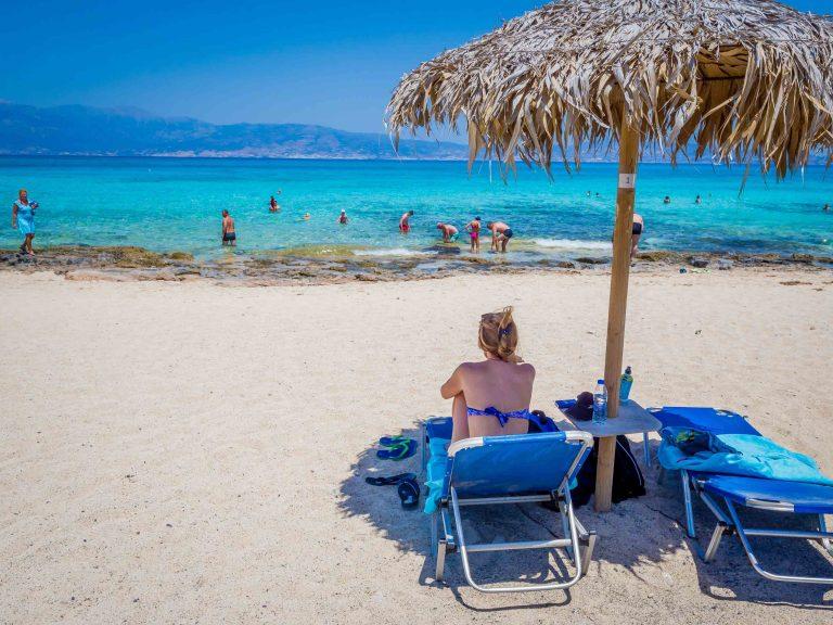 Nainen bikineissä aurinkovarjon alla Chrissin saaren rannalla