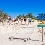 Ihmisiä kulkemassa jonossa Chrissin saaren rannalle aurinkoisessa säässä