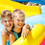 Kaksi tyttöä uimarenkaiden kanssa vesipuistossa