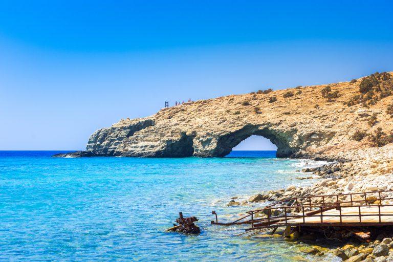 Näkymä rannalta kalliomuodostelmalle, jonka päällä ihmisiä katsomassa merta