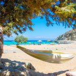 Riippumatto puun varjossa hiekkarannalla, taustalla turkoosi meri ja ihmisiä aurinkovarjojen alla.