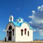 Pieni sinivalkoinen kirkko autiolla hiekkakentällä