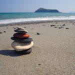 Litteitä kiviä kasattu pieneksi torniksi, taustalla meri