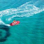 Pariskunta tekee U-käännöksen vesiskootterilla kirkkaassa vedessä