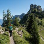 Huivipäinen nainen kulkee reppu selässä korkealla vuoristoisella polulla.